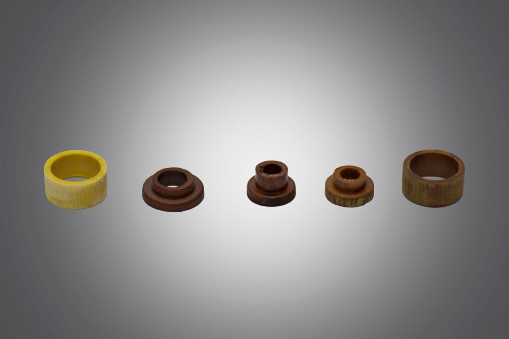 yellow, dark brown and light brown circular thermoset injection molded componenet displayed in grey background