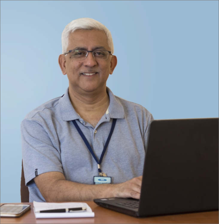 Mr. M. P Krishnan- Chairman & managing director of Techplaastic industrie pvt Ltd -best plastic molding manufacturer in India working on laptop displayed  under light blue background