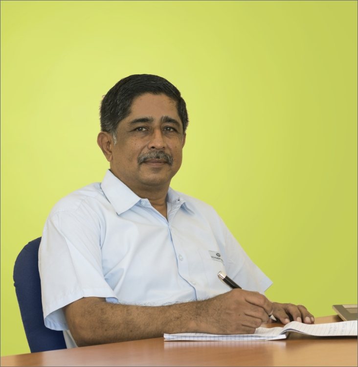 Mr M.P Sankar-Director of operations of Techplaastic Industrie Pt Ltd -best plastic molding manufacturer in India writing with black pen on the notebook displayed in light green background