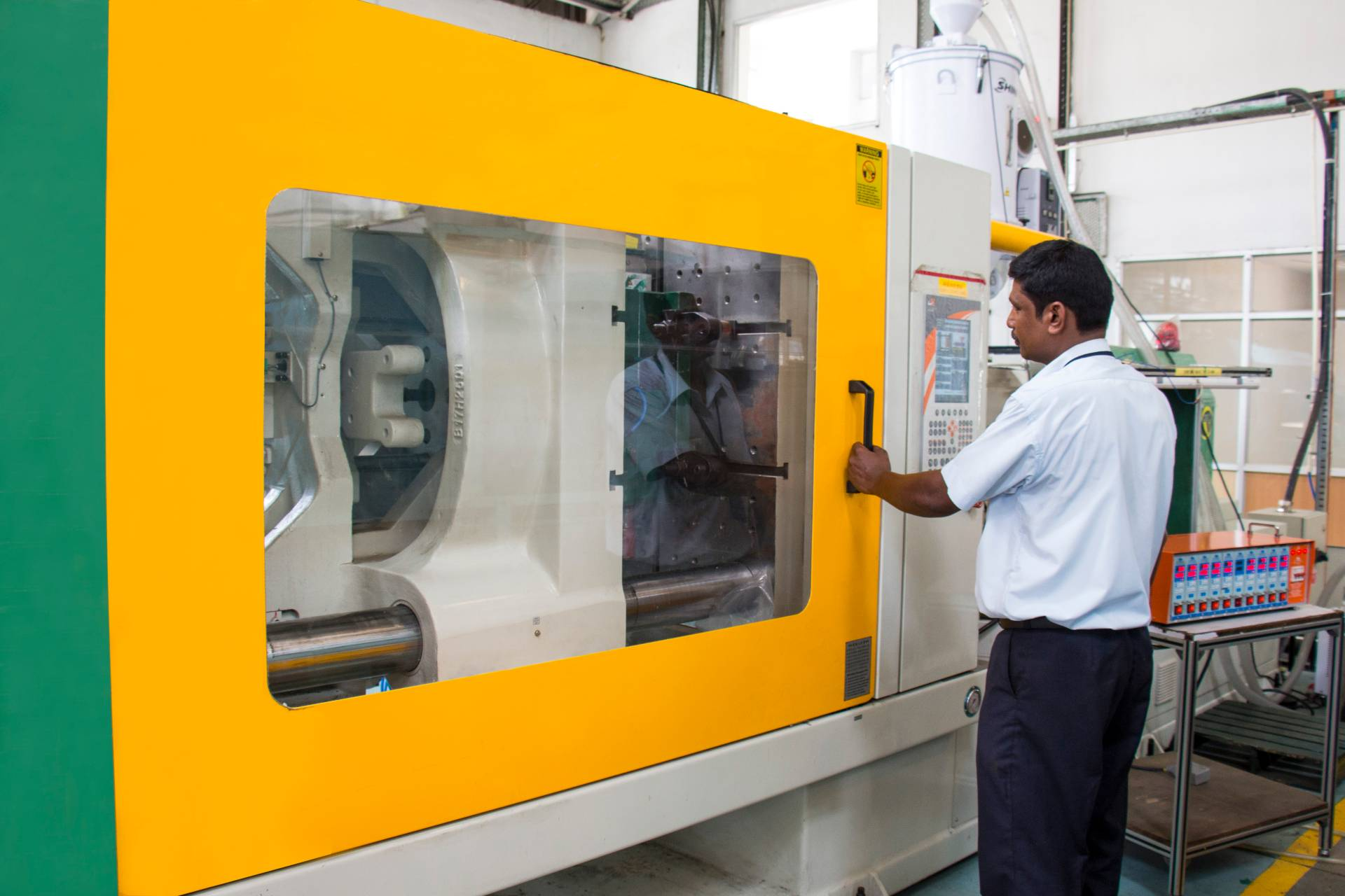 Professional operating the Thermoset Injection moulding machine at the leading plastic moulding company in India